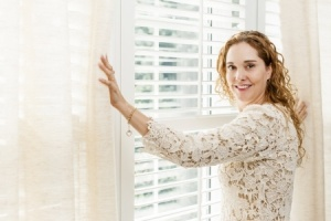 woman standing at window looking at blinds - window treatments